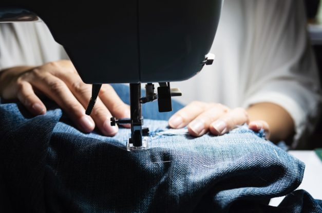 Woman doing jeans patchwork using sewing machine - home DIY sewing concept